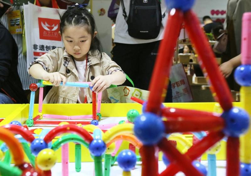 """当日,为期3天的第20届北京国际玩具及幼教用品展览会暨北京国际幼儿园用品及配套设备展览会在中国国际展览中心开幕,来自20多个国家和地区的上百个知名品牌厂商参展。  5月12日,小朋友们在展览会上与一款供幼儿园使用的机器人互动。  5月12日,一名小朋友在展览会上体验""""光纤传送""""。  5月12日,工作人员在展览会上介绍展出的机器人。  5月12日,工作人员在展览会上介绍展出的机器人。  5月12日,一名家长抱着孩子欣赏手工制作的京剧脸谱摆件。"""